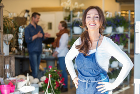 Portrait of smiling female owner with customers in background at flower shop
